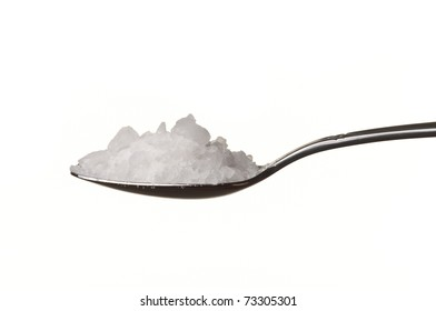 Rock salt in a spoon isolated over white background