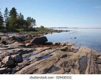 Rock sea coast at the sunny day. White Sea. Karelia. Russia