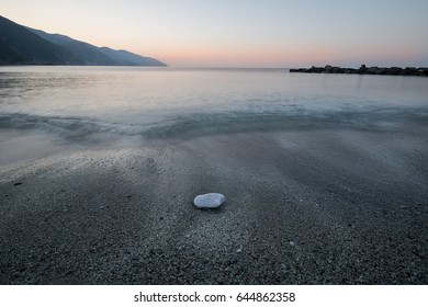 A rock and sea waves in sunrise