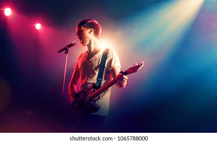 Rock singer with a guitar in stage lights