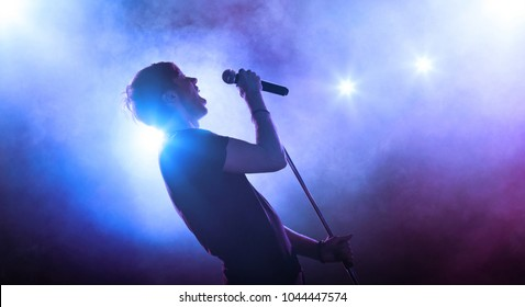 Rock singer performing on stage with microphone