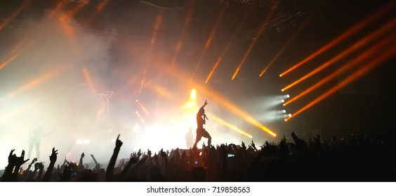 Rock singer  standing on crowd at music concert and light show.