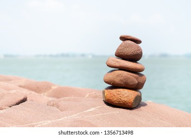 Rock stack on the stone courtyard with blur sea and sky background on the sunshine day. Balance stones against the sea.