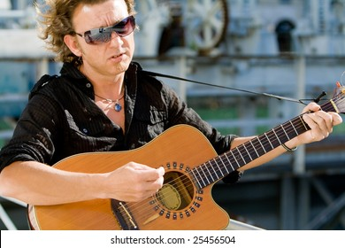 Rock star with acoustic guitar performing live in the summer