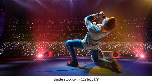 Rock star celebrity on the main stage big music festival. Aroun full stadium of spectators. fans are holding flashlights