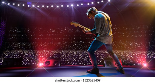 Rock star celebrity on the main stage big music festival. Aroun full stadium of spectators. fans are holding flashlights