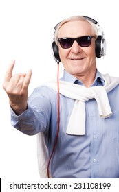 Rock star. Cheerful senior man in headphones listening to music and showing hand sign while standing against white background