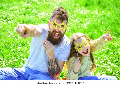 Rock star concept. Family spend leisure outdoors. Child and dad posing with star shaped eyeglases photo booth attribute at meadow. Father and daughter sits on grass at grassplot, green background