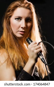 Rock star girl singing to the microphone in a studio