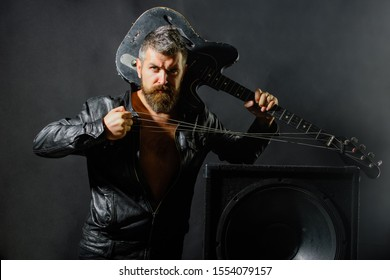 Rock star with guitar. Music festival. Music, concert, entertainment. Guitarist with electric bass guitar. Music, musical instrument. Handsome rock star wearing leather jacket holds electric guitar