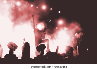 The rock star guitarist on the big stage shows the sign of the horn. Silhouette in red bright light and smoke.