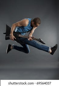 rock star jumping and playing an electric guitar