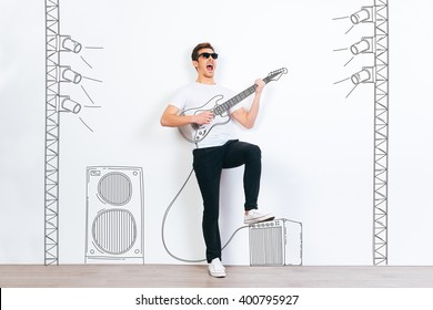 Rock star! Young handsome man in sunglasses playing drawn guitar and keeping mouth open while standing against white background with illustration of stereo column and stage light