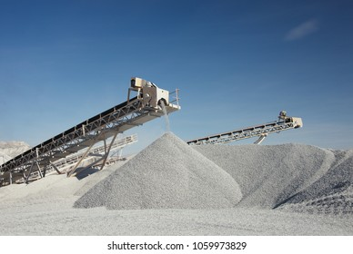 Rock stone crushing machine against a blue sky, close-up. Mining industry. Quarry and mining equipment.