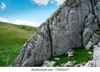Rock stone on mountain plateau. Grass and bushes grow around. Summertime for travelling and hiking.