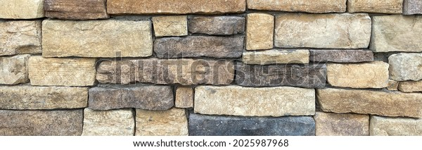 a rock stone wall building facade structure with black brown and tan cut rock bricks