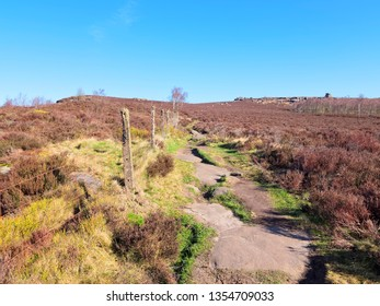 A rock strewn footpath runs up hill between a wire fence and dark brown heather acorss the Derbyshire Peak District.