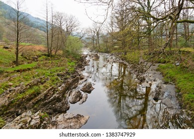 The rock strewn River Mawddach flows between tree lined banks in the Welsh countryside
