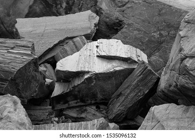 Rock structure close up. Pile of big gray stones on norwegian beach. Texture on the rock surface. Black and white abstract composition.  Stone glowing with light. Monochromatic.