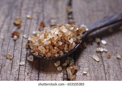 rock sugar. crystalline sugar. sugar on vintage wood background. rock sugar in wooden spoon on vintage wood background