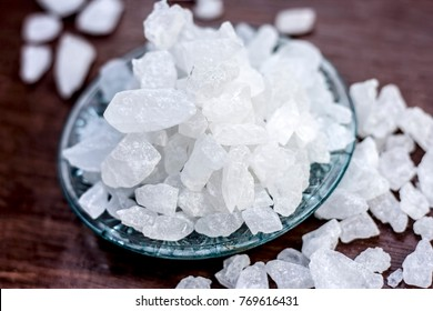 Rock sugar or sugar cubes in a glass plate on wooden surface.