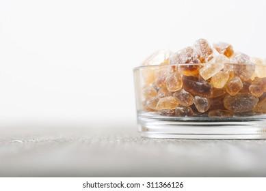 rock sugar in glass pot, on dark wooden surface