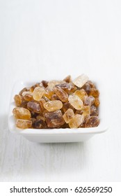 rock sugar in square dish, on white  wooden surface