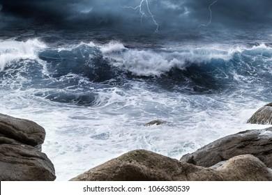rock in the surf dark blue ocean sea high waves thunderstorm bad weather background