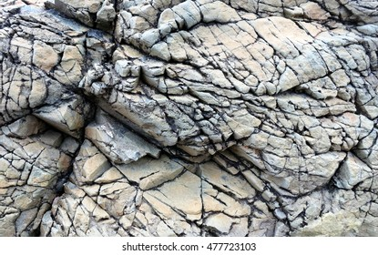 Rock textured with deep cracks and shades of grey along the coast of Llanddwyn Island, Anglesey, Wales.
