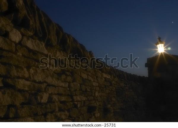 Rock wall entrance on a farm at night.