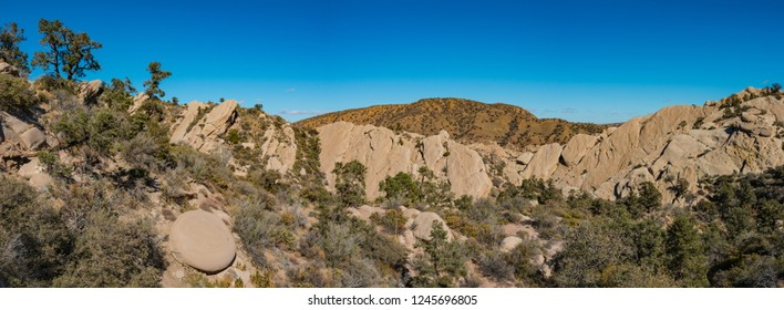 Rock wall in the Mojave desert wilderness made of brown sandstone.