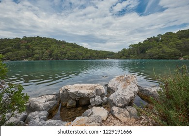 Rock in the water with a cloudy sky in the Mljet National Park in Croatia