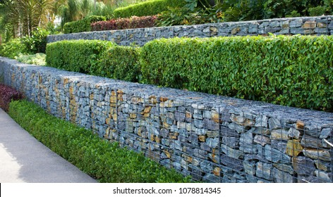 Rock and wire gabions used as retaining walls in a multi tiered garden design
