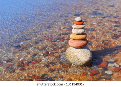 Rock zen pyramid of colorful pebbles standing in the water on the background of the sea. Concept of balance, harmony and meditation