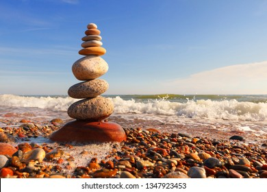 Rock zen pyramid of multi-colored pebbles in the pink rays of the setting sun against the sea. Concept of balance, harmony and meditation