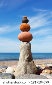 Rock zen pyramid of red and pink pebbles on the beach. Concept of Life balance, harmony and meditation