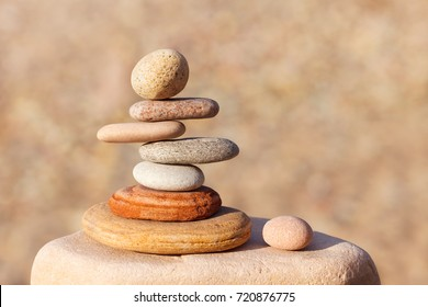 Rock zen pyramid of white, red and yellow stones. Concept of balance, harmony and meditation. Soft focus, selective focus