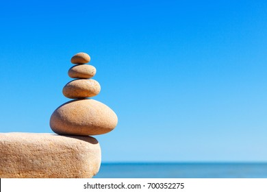 Rock zen pyramid of yellow stones on a background of blue sky and sea. Concept of balance, harmony and meditation