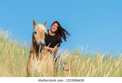 Rockanje,Holland,02-jul-2018:eighteen year old girl a haflinger horse posing with the dunes as background