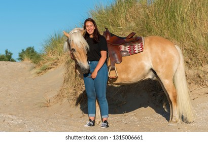 Rockanje,Holland,02-jul-2018:eighteen year old girl posing with her haflinger horse on the beach with the dunes as background
