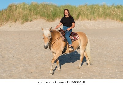 Rockanje,Holland,02-jul-2018:eighteen year old girl riding on a haflinger horse on the beach with the dunes as background