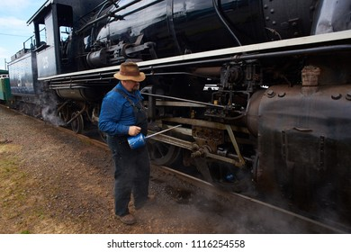 ROCKAWAY BEACH, OREGON-JUNE 15, 2018: An oiler oils the old steam locomotive operated by the Oregon Coast Scenic Railway at its destination in Rockaway Beach.