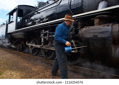ROCKAWAY BEACH, OREGON-JUNE 15, 2018: An oiler lubricates the old steam locomotive operated by the Oregon Coast Scenic Railway at its destination in Rockaway Beach.