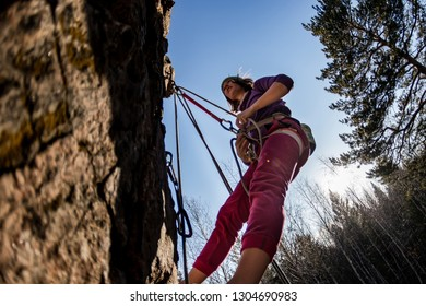 rock-climber girl crying in pain hanging on a rope with a sad face when climbing on a rock