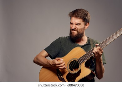 Rocker with a beard playing the guitar on a gray background