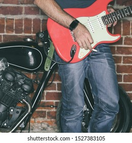 A rocker guitarist plays an electric guitar in a garage next to a motorcycle. Concept rock music and old school bike.