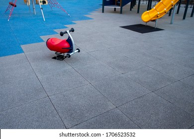 rocker toy rider in a children's public playground with rubber tiled mats