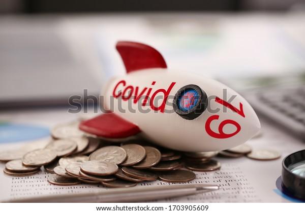 Cohete con inscripción Covid 19 cayó sobre un montón de monedas de fondo. Concepto de crisis financiera mundial