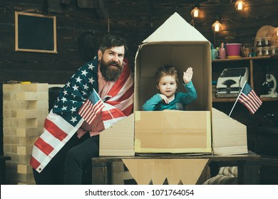 Rocket launch concept. Kid happy sit in hand made rocket with usa flags, wave hand. Child cute boy play cosmonaut, astronaut. American family with usa flags play with rocket made out of cardboard box.