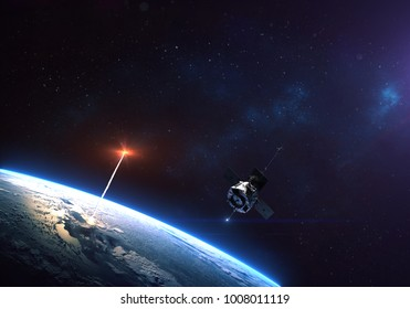 Rocket launch from the Earth planet through the clouds with a bright glow of the engine and a satellite on the orbit and a bright blue nebula galaxy. Elements of this image furnished by NASA